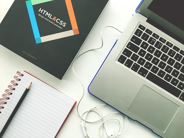 ordenador portálil junto a un bloc de notas y un libro de construcción web coon HTML y CSS